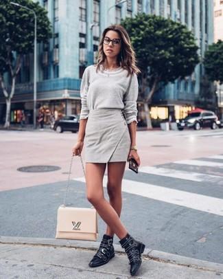 Come indossare: maglione girocollo grigio, minigonna grigia, stivaletti in pelle con borchie neri, cartella in pelle beige