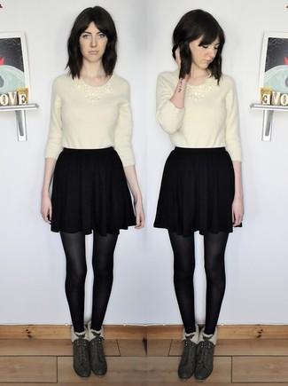 Come indossare: maglione girocollo morbido beige, gonna a pieghe nera, stivaletti in pelle scamosciata verde scuro