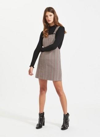 Come indossare: maglione girocollo nero, scamiciato scozzese grigio, stivaletti in pelle neri