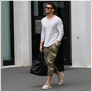 Come indossare e abbinare: maglione girocollo bianco, pantaloni sportivi mimetici verde oliva, sneakers basse beige, borsone in pelle nero