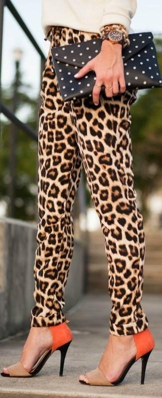 Come indossare e abbinare: maglione girocollo beige, pantaloni stretti in fondo leopardati marrone chiaro, sandali con tacco in pelle scamosciata marrone chiaro, pochette a pois nera e bianca