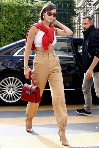 Come indossare e abbinare: maglione girocollo rosso, top corto bianco, pantaloni stretti in fondo marrone chiaro, décolleté in pelle beige