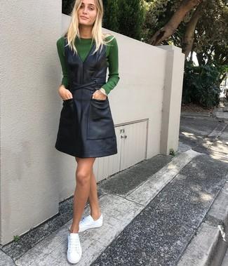 Come indossare: maglione girocollo verde scuro, scamiciato in pelle nero, sneakers basse in pelle bianche