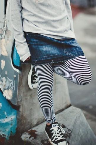 Come indossare: maglione grigio, gonna di jeans blu scuro, leggings a righe orizzontali bianchi e neri, sneakers nere e bianche