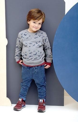 Come indossare e abbinare: maglione stampato grigio, t-shirt manica lunga rossa, pantaloni sportivi blu, sneakers rosse
