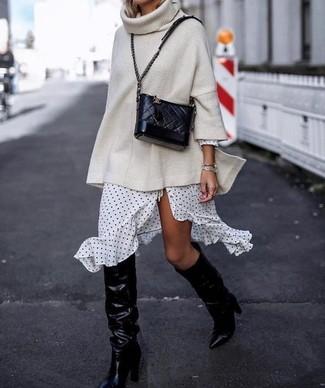 Come indossare e abbinare: maglione oversize lavorato a maglia beige, vestito a portafoglio a pois bianco e nero, stivali al ginocchio in pelle neri, borsa a tracolla in pelle trapuntata nera