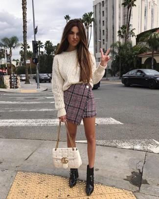 Trend da donna 2021: Un maglione oversize lavorato a maglia bianco e una minigonna di tweed rosa per essere spensierata e alla moda. Stivaletti in pelle neri sono una eccellente scelta per completare il look.