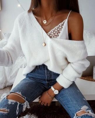 Come indossare: maglione oversize lavorato a maglia bianco, canotta di pizzo bianca, jeans strappati blu, collana con ciondolo dorata