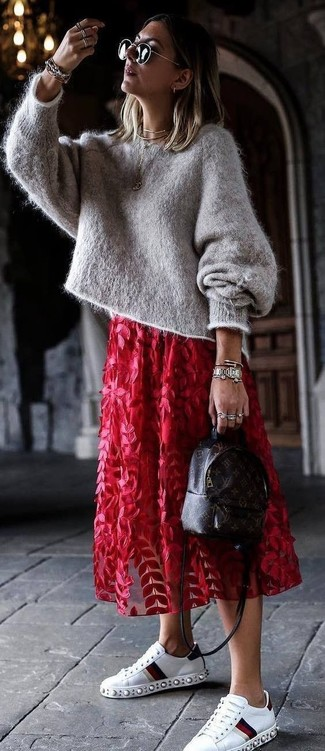 Come indossare: maglione oversize in mohair grigio, gonna longuette in tulle a fiori rossa, sneakers basse in pelle decorate bianche, zaino in pelle stampato marrone scuro