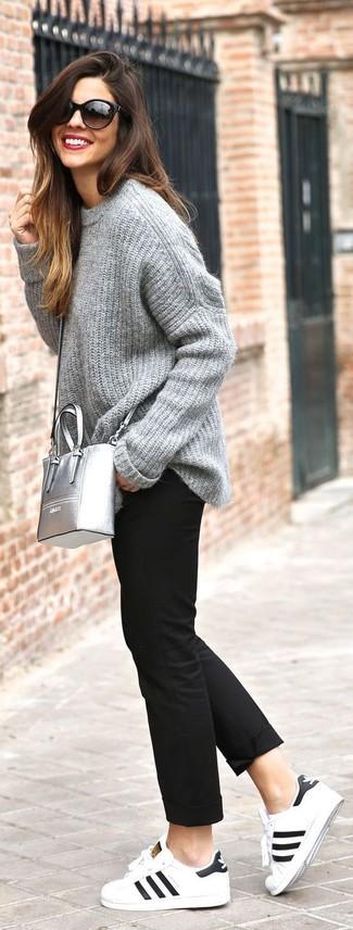 Come indossare: maglione oversize lavorato a maglia grigio, chino neri, sneakers basse in pelle bianche e nere, borsa a tracolla in pelle argento