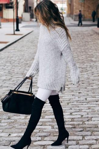 Come indossare: maglione oversize lavorato a maglia grigio, jeans aderenti bianchi, stivali sopra il ginocchio in pelle scamosciata neri, cartella in pelle scamosciata nera