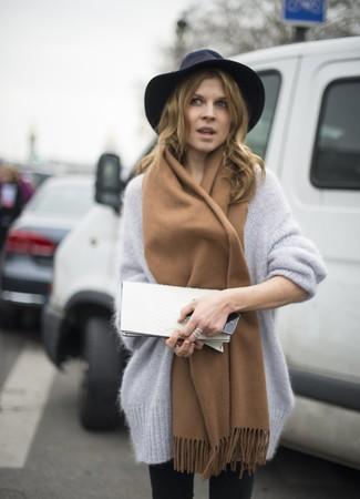 Come indossare e abbinare: maglione oversize in mohair grigio, jeans aderenti neri, pochette in pelle bianca, borsalino di lana nero