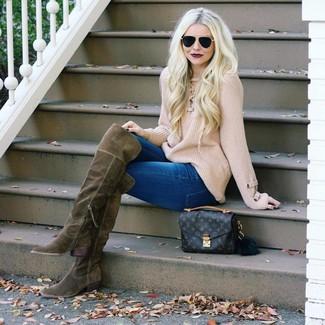 Come indossare e abbinare: maglione oversize lavorato a maglia beige, jeans aderenti blu, stivali sopra il ginocchio in pelle scamosciata verde oliva, cartella in pelle stampata marrone scuro