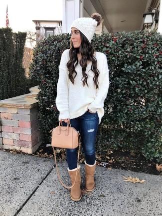 Come indossare e abbinare: maglione oversize lavorato a maglia bianco, jeans aderenti strappati blu scuro, stivali ugg marrone chiaro, borsa shopping in pelle rosa