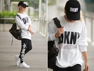 Come indossare: maglione oversize stampato bianco, leggings stampati neri, sneakers basse bianche, borsa shopping in pelle nera