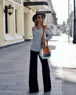 Come indossare: maglione oversize tagliato grigio, pantaloni larghi neri, borsa a tracolla in pelle marrone, borsalino di lana grigio scuro