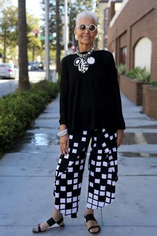 Come indossare e abbinare: maglione oversize nero, pantaloni larghi a quadri neri e bianchi, sandali piatti in pelle neri, occhiali da sole bianchi
