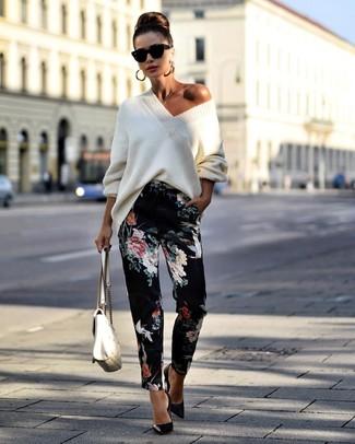 Come indossare e abbinare: maglione oversize lavorato a maglia bianco, pantaloni stretti in fondo a fiori neri, décolleté in pelle neri, cartella in pelle trapuntata bianca