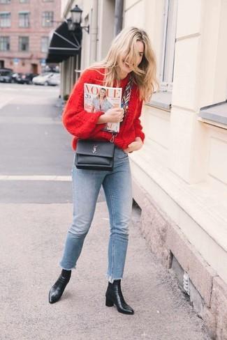 Come indossare: maglione oversize lavorato a maglia rosso, jeans aderenti azzurri, stivaletti in pelle neri, borsa a tracolla in pelle nera