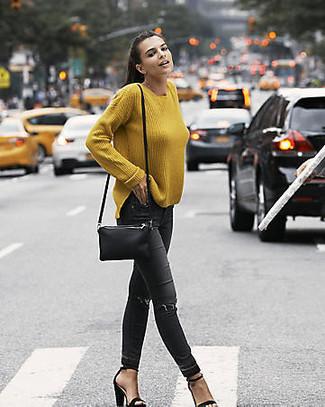 Come indossare: maglione oversize senape, jeans aderenti strappati neri, sandali con tacco in pelle scamosciata neri, borsa a tracolla in pelle nera