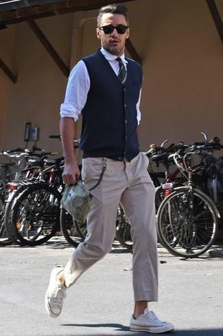 Come indossare e abbinare chino beige: Mostra il tuo stile in un maglione senza maniche blu scuro con chino beige per un look davvero alla moda. Scegli un paio di sneakers basse di tela beige come calzature per un tocco più rilassato.