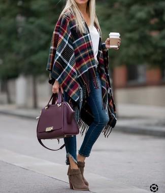 Come indossare: mantello scozzese multicolore, maglione con scollo a v bianco, jeans aderenti blu scuro, stivaletti in pelle scamosciata marroni