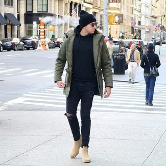 Come indossare e abbinare: parka verde oliva, felpa con cappuccio nera, jeans aderenti strappati neri, stivali chelsea in pelle scamosciata marrone chiaro