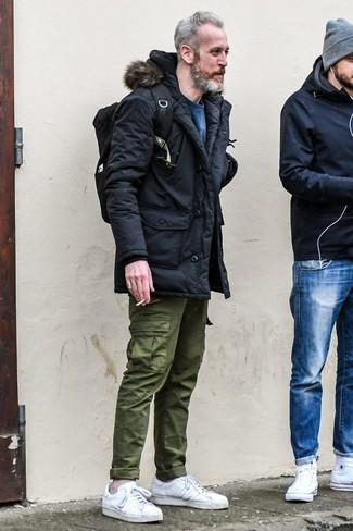 Come indossare e abbinare: parka nero, felpa blu, pantaloni cargo verde oliva, sneakers basse in pelle bianche