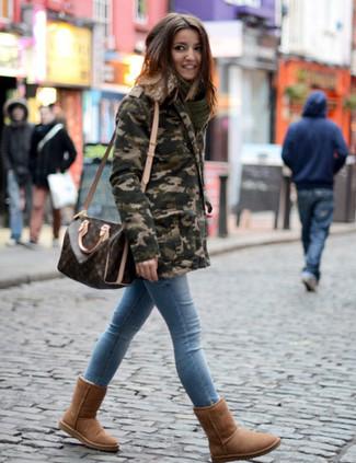 Come indossare e abbinare: parka mimetico verde oliva, jeans aderenti azzurri, stivali ugg marroni, borsone in pelle stampato marrone scuro