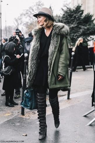 Come indossare: parka verde oliva, maglione con scollo a v nero, gonna a pieghe nera, stivali sopra il ginocchio in pelle neri