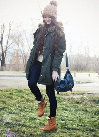 Come indossare: parka verde scuro, maglione girocollo beige, jeans aderenti blu scuro, stivali piatti stringati in pelle marrone chiaro
