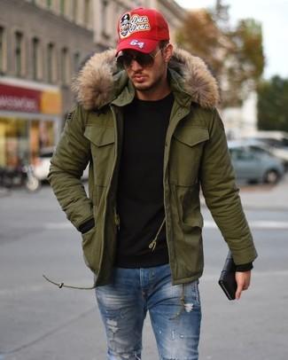 Come indossare e abbinare: parka verde oliva, maglione girocollo nero, jeans aderenti strappati blu, berretto da baseball stampato rosso