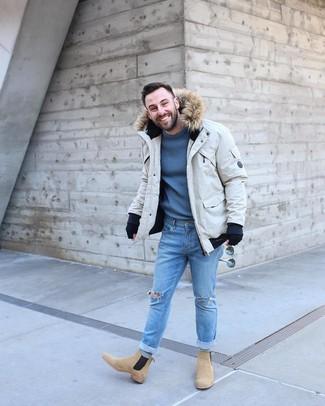 Come indossare e abbinare: parka beige, maglione girocollo blu, jeans aderenti strappati azzurri, stivali chelsea in pelle scamosciata marrone chiaro