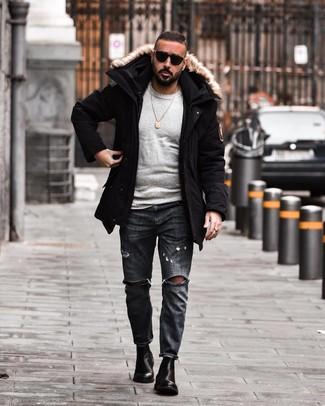 Come indossare e abbinare jeans strappati grigio scuro: Scegli un outfit composto da un parka nero e jeans strappati grigio scuro per un look perfetto per il weekend. Indossa un paio di stivali chelsea in pelle neri per un tocco virile.