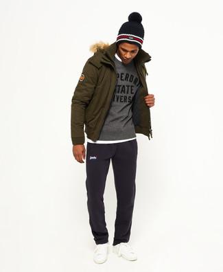 Come indossare e abbinare: parka verde oliva, maglione girocollo stampato grigio, t-shirt girocollo bianca, pantaloni sportivi blu scuro