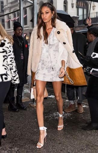Come indossare e abbinare: pelliccia beige, vestito a trapezio a fiori bianco, sandali con tacco in pelle bianchi, cartella in pelle marrone chiaro