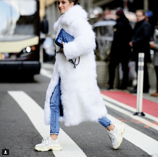Come indossare: pelliccia bianca, jeans aderenti blu, scarpe sportive bianche, borsa a tracolla in pelle blu