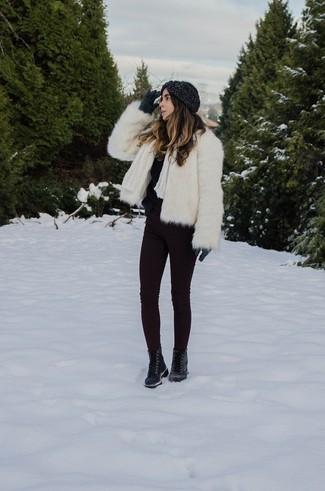 Come indossare: pelliccia corta bianco, maglione girocollo morbido nero, jeans aderenti melanzana scuro, stivali piatti stringati in pelle neri