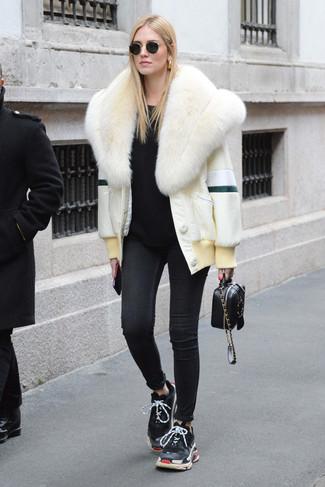 Come indossare: pelliccia corta bianco, maglione girocollo nero, jeans aderenti neri, scarpe sportive nere