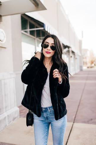 Come indossare: pelliccia corta nero, t-shirt manica lunga grigia, jeans aderenti azzurri, borsa a tracolla in pelle trapuntata nera