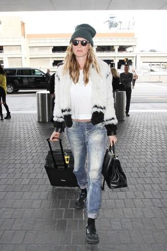 Come indossare: pelliccia corta bianco e nero, t-shirt manica lunga bianca, jeans strappati blu, sneakers basse in pelle nere