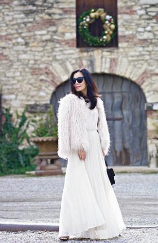 Come indossare: pelliccia corta bianco, vestito lungo a pieghe bianco, sabot in pelle scamosciata neri, pochette in pelle scamosciata nera