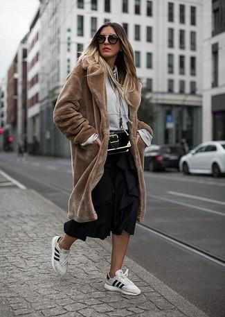 Come indossare: pelliccia marrone, felpa con cappuccio grigia, gonna longuette a pieghe nera, sneakers basse in pelle bianche