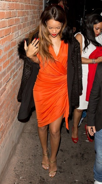 Come indossare: pelliccia nera, vestito a portafoglio arancione, sandali con tacco in pelle dorati