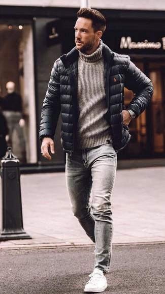 Come indossare e abbinare: piumino nero, dolcevita di lana lavorato a maglia grigio, jeans aderenti grigi, sneakers basse in pelle bianche