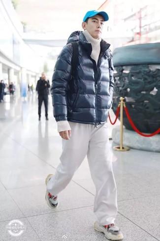 Come indossare: piumino blu scuro, dolcevita lavorato a maglia bianco, pantaloni sportivi bianchi, scarpe sportive grigie