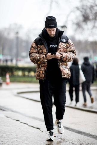 Trend da uomo: Opta per un piumino mimetico marrone e chino neri, perfetto per il lavoro. Opta per un paio di scarpe sportive bianche per avere un aspetto più rilassato.