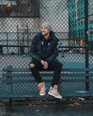 Come indossare: piumino nero, felpa con cappuccio stampata blu scuro, jeans aderenti strappati neri, sneakers alte in pelle marrone chiaro