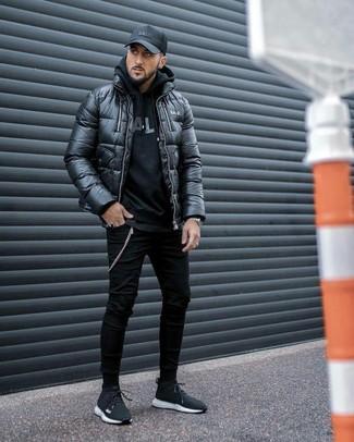 Come indossare: piumino nero, felpa con cappuccio stampata nera, t-shirt girocollo nera, jeans aderenti neri