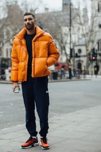 Trend da uomo: Prova a combinare un piumino arancione con pantaloni sportivi blu scuro per un outfit comodo ma studiato con cura. Scarpe sportive arancioni aggiungono un tocco particolare a un look altrimenti classico.